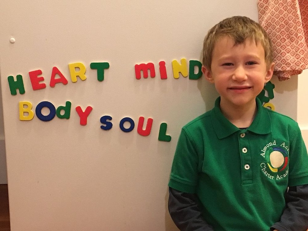 Almond Acres Charter Academy young student stands next to a magnetic board with the words heart, mind, body, and soul spelled out