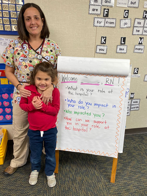 A parent poses with her daughter during a visit to Almond Acres to share about her profession as a Registered Nurse.