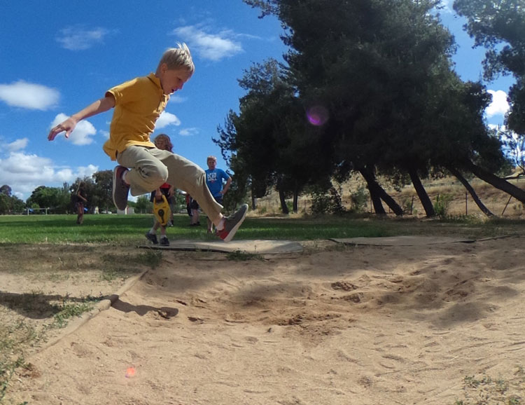 An Almond Acres Charter Academy student takes a huge leap into a sand pit
