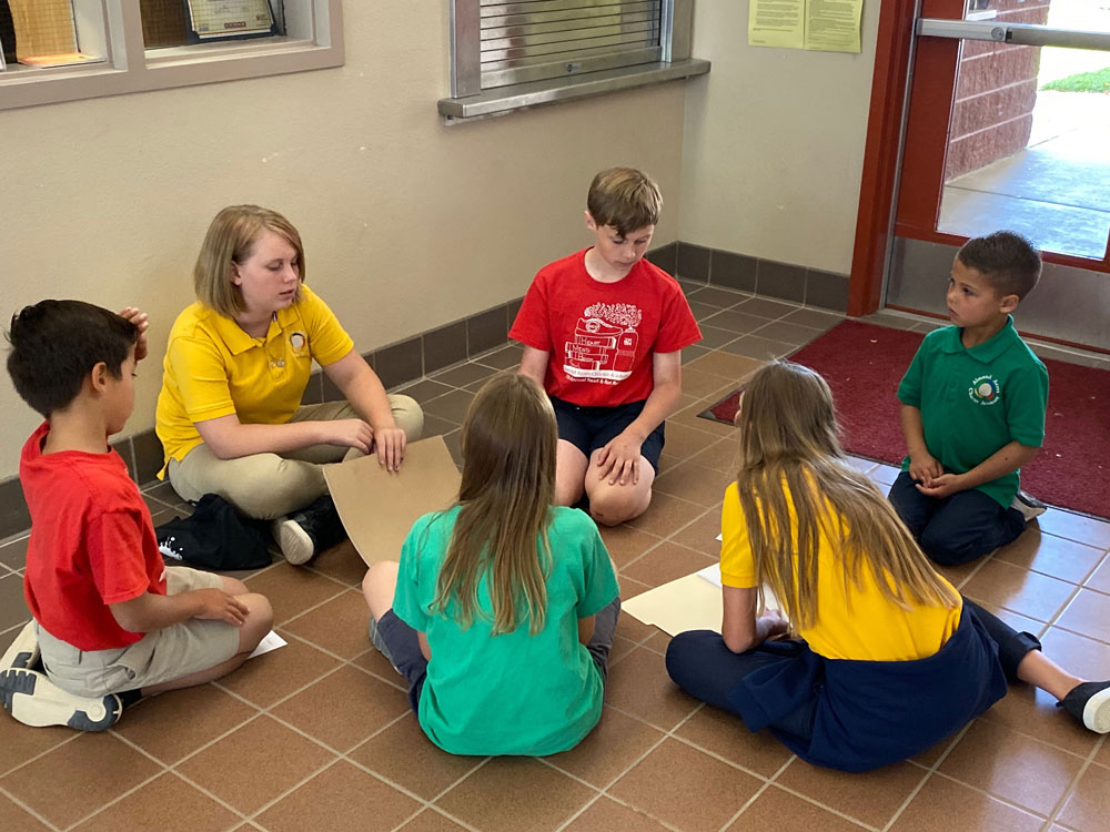 Six Almond Acres Charter Academy students of varying ages sit together on the floor in a circle to work on a project.